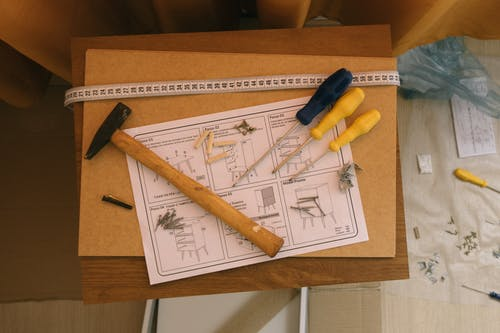 tools and blueprint to build a house with hammer